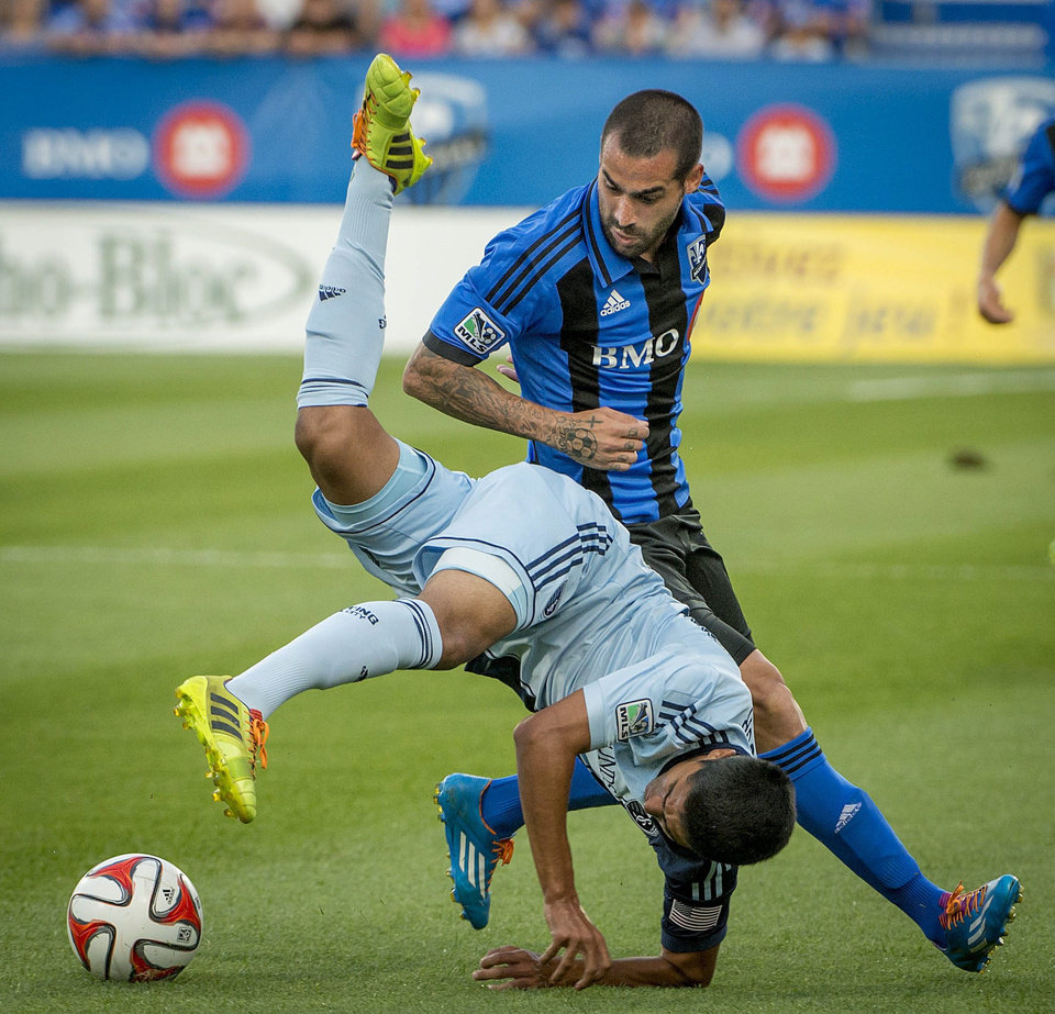 Photo - Sporting Kansas City's Igor Juliao flips through the air as Montreal Impact's Andres Romero looks on during the first half of a soccer game, Saturday, July 12, 2014 in Montreal. (AP Photo/The Canadian Press, Peter McCabe)