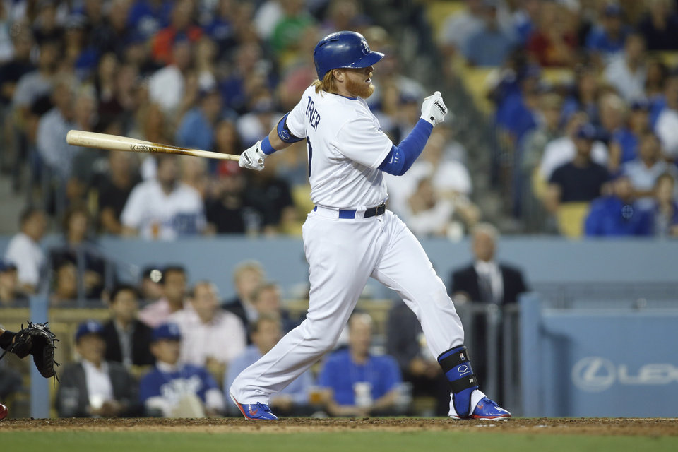 Photo - Los Angeles Dodgers' Justin Turner follows through on a single to score Juan Uribe against the St. Louis Cardinals during the eighth inning of a baseball game, Thursday, June 26, 2014, in Los Angeles. (AP Photo/Danny Moloshok)