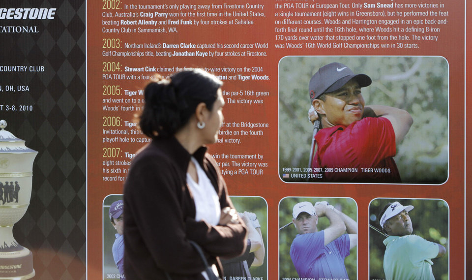 Photo - A patron looks at a photo of Tiger Woods  as she walks past a billboard of past Match Play champions entering the grounds at  the Match Play Championship golf tournament Friday, Feb. 19, 2010, in Marana, Ariz. Woods has apologized for having affairs and says he is unsure when he will return to competitive golf. Woods spoke for more than 13 minutes Friday, Feb. 19, 2010,  from the clubhouse at the TPC Sawgrass, home of the PGA Tour.  (AP Photo/Nam Y. Huh) ORG XMIT: AZLI102