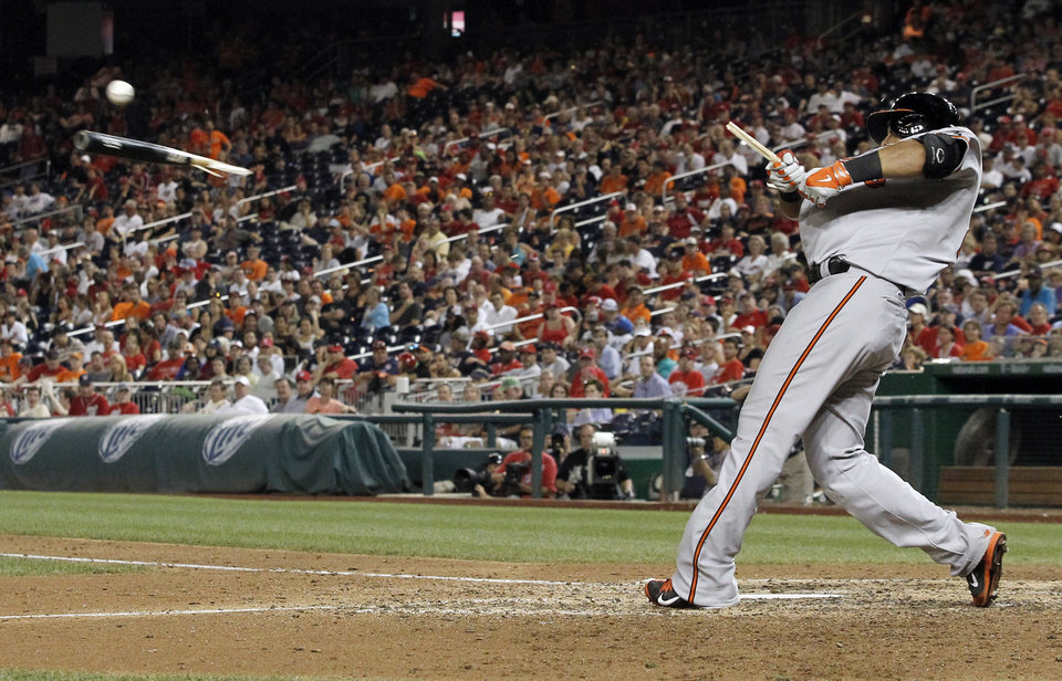 Photo - Baltimore Orioles' Nelson Cruz breaks his bat as he hits a single during the 11th inning of an interleague baseball game against the Washington Nationals at Nationals Park, Monday, July 7, 2014, in Washington. The Orioles won 8-2, in 11 innings. (AP Photo/Alex Brandon)