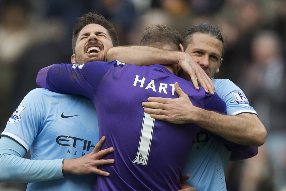 Photo - Manchester City's Javier Garcia, left, and Martin Demichelis, right, celebrate with goalkeeper Joe Hart after their 2-0 win against Hull City in their English Premier League soccer match at the KC Stadium, Hull, England, Saturday March 15, 2014. (AP Photo/Jon Super)