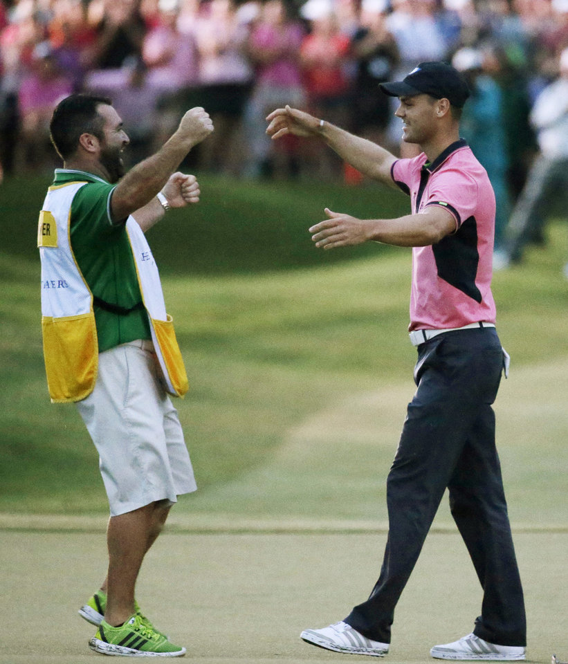 Photo - Martin Kaymer of Germany, left, celebrates with his caddie Craig Connelly after winningThe Players championship golf tournament at TPC Sawgrass, Sunday, May 11, 2014 in Ponte Vedra Beach, Fla. (AP Photo/John Raoux)