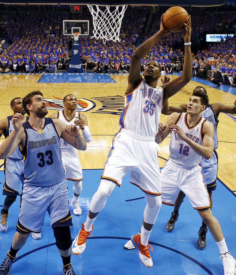 Photo - Oklahoma City's Kevin Durant (35) shoots between Steven Adams (12) and Memphis' Marc Gasol (33) during Game 7 in the first round of the NBA playoffs between the Oklahoma City Thunder and the Memphis Grizzlies at Chesapeake Energy Arena in Oklahoma City, Saturday, May 3, 2014. The Thunder won 120-109. Photo by Nate Billings, The Oklahoman