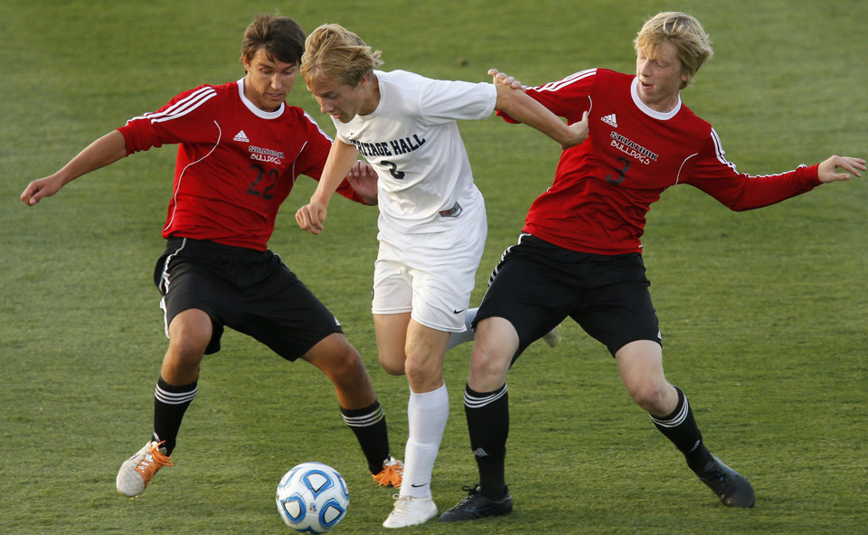 Photo - Heritage Hall's Davis Angel goes between Skiatook's Hayden Reed, left, and Dominic Seabolt during the Class 5A boys soccer championship between Heritage Hall and Skiatook in Norman, Okla., Friday, May 16, 2014. Photo by Bryan Terry, The Oklahoman