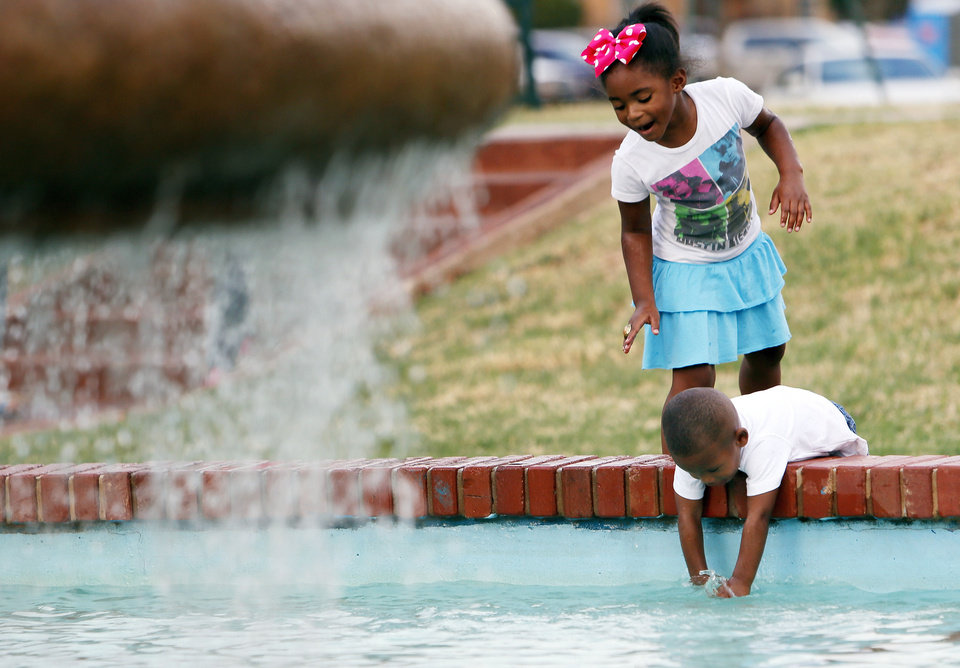 Photo - Tamiya Oliver, 5, watches her brother, Prince John Oliver, 2, dip his hands in a fountain during the Arts in the City Multicultural Festival at Memorial Park on Saturday. PHOTOS BY NATE BILLINGS, THE OKLAHOMAN