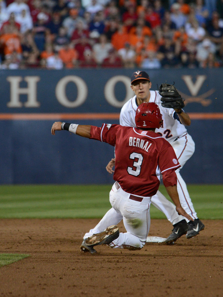 Photo - Arkansas's Michael Bernal (3) is tagged out at second by Virginia's Daniel Pinero during the third inning of an NCAA college baseball regional tournament game in Charlottesville, Va., Saturday, May 31, 2014. (AP Photo/Pat Jarrett)