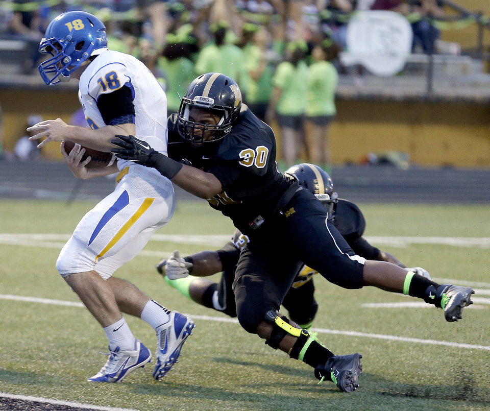 Photo - Stillwater's Braxton Noble gets by Midwest City's Camron Carson as he scores a touchdown during the high school football game between Midwest City and Stillwater at Midwest City, Okla., Friday, Sept. 13, 2013. Photo by Sarah Phipps, The Oklahoman