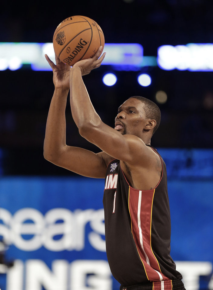 Photo - Chris Bosh, of the Miami Heat (1) shoots during the skills competition at the NBA All Star basketball game, Saturday, Feb. 15, 2014, in New Orleans. (AP Photo/Gerald Herbert)