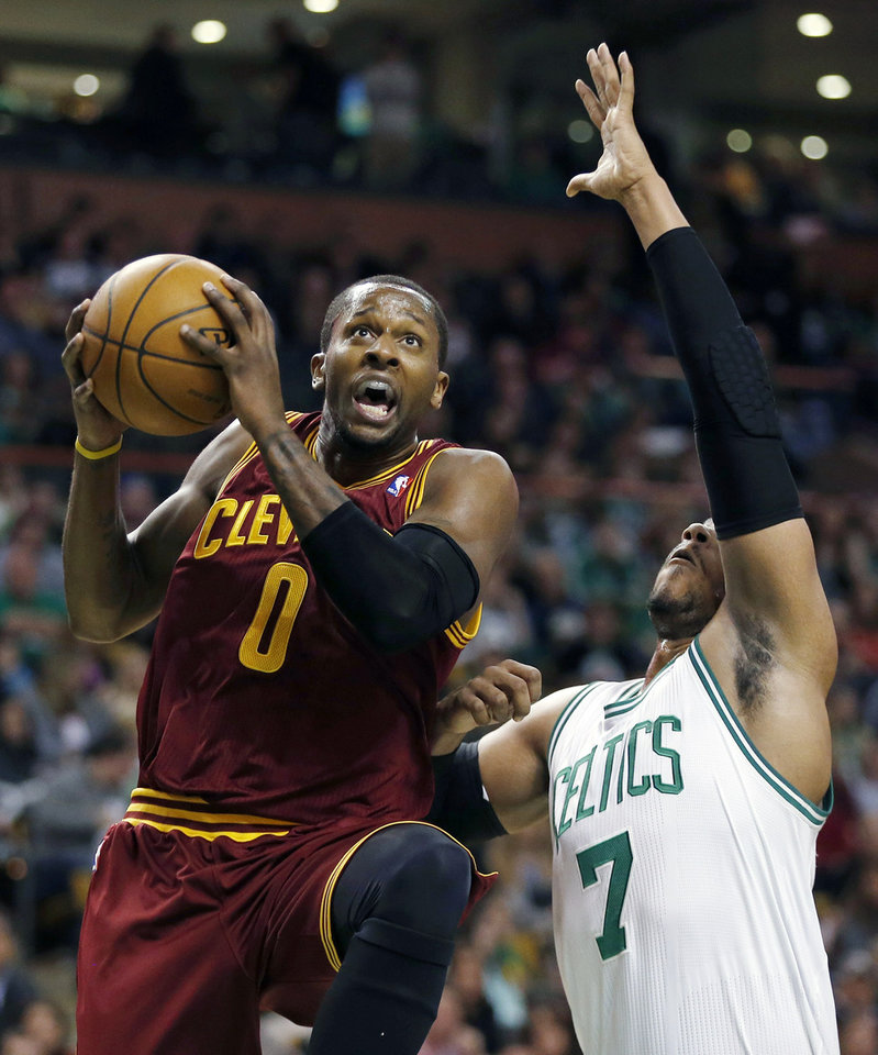 Photo - Cleveland Cavaliers' C.J. Miles (0) goes up to shoot in front of Boston Celtics' Jared Sullinger (7) during the first quarter of an NBA basketball game in Boston, Saturday, Dec. 28, 2013. (AP Photo/Michael Dwyer)