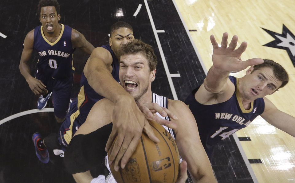 Photo - San Antonio Spurs' Tiago Splitter, center, of Brazil, is fouled by New Orleans Pelicans' Anthony Davis, center back, as he tries to shoot during the first half of an NBA basketball game, Monday, Nov. 25, 2013, in San Antonio. Pelicans' Al-Farouq Aminu (0) and Jason Smith (14) look on. (AP Photo/Eric Gay)