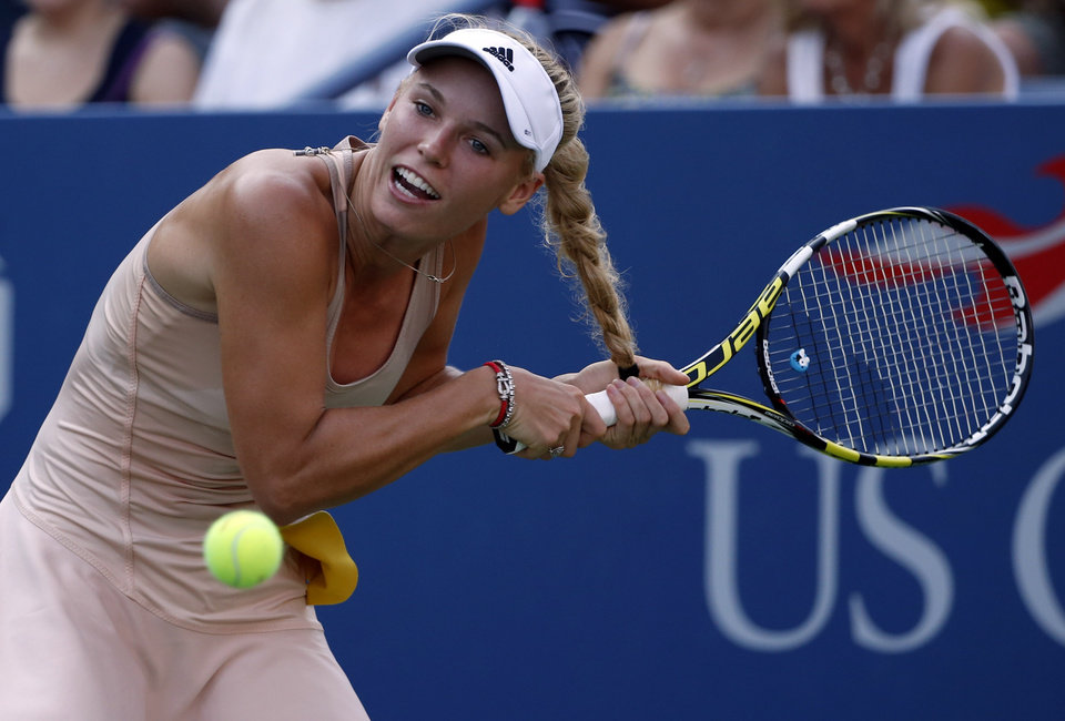 Photo - Caroline Wozniacki, of Denmark, gets her hair caught in her racket as she tries to return a shot to Aliaksandra Sasnovich, of Belarus, during the second round of the 2014 U.S. Open tennis tournament, Wednesday, Aug. 27, 2014, in New York. (AP Photo/Kathy Willens)