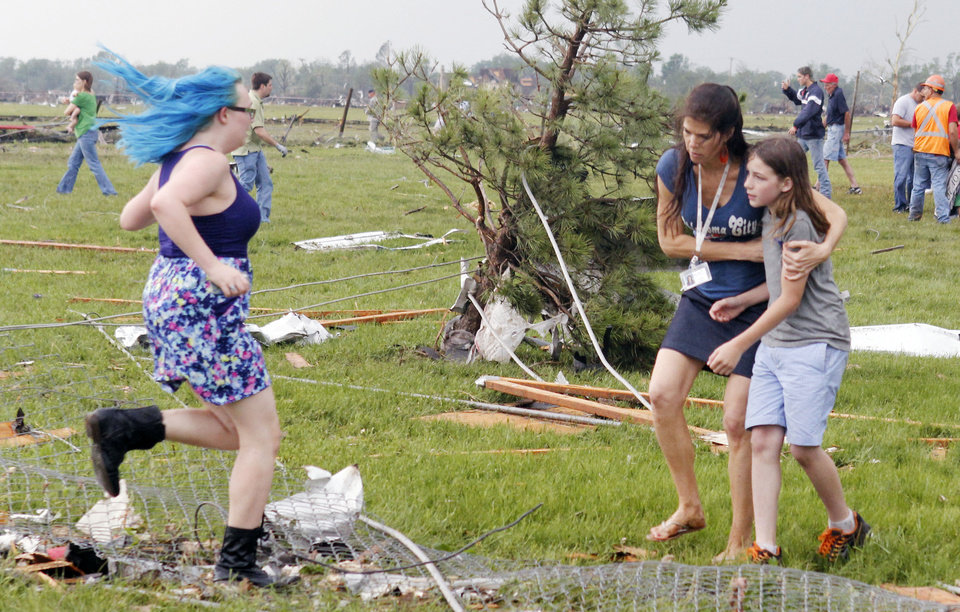 Photo - Lily Raymond ,17, rushes to embrace her brother Ethan, 11, outside of Briarwood Elementary school after a tornado destroyed the school in south  Oklahoma City, Okla, Monday, May 20, 2013.  PAUL HELLSTERN - The Oklahoman