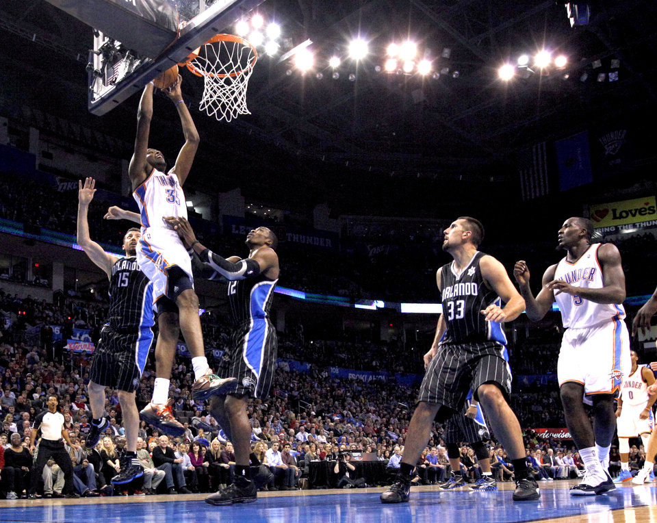 Oklahoma City Thunder's Kevin Durant (35) dunks in between Orlando Magic's Hedo Turkoglu (15) and Dwight Howard (12) during the opening day NBA basketball game between the Oklahoma CIty Thunder and the Orlando Magic at Chesapeake Energy Arena in Oklahoma City, Sunday, Dec. 25, 2011. Photo by Sarah Phipps, The Oklahoman