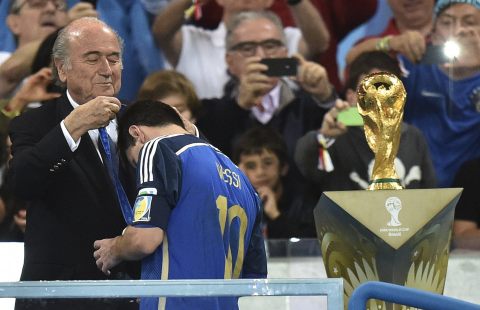 Photo - Argentina's Lionel Messi gets his runners-up medal from FIFA President Sepp Blatter after the World Cup final soccer match between Germany and Argentina at the Maracana Stadium in Rio de Janeiro, Brazil, Sunday, July 13, 2014. Germany won the match 1-0. (AP Photo/Martin Meissner)