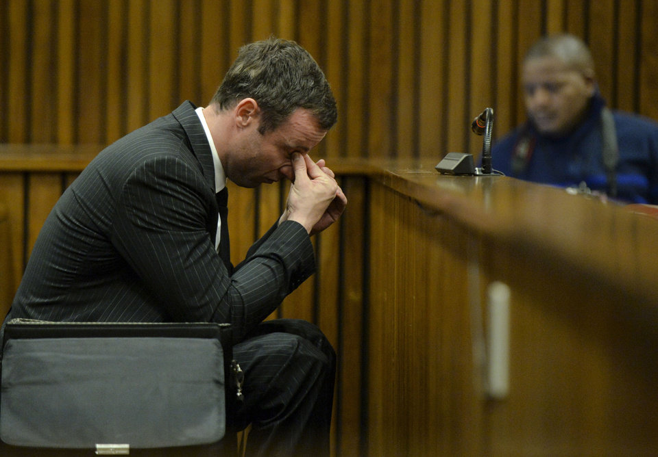 Photo - Oscar Pistorius, gestures, as he sits in court, during his trial in Pretoria, South Africa, Friday, Aug. 8, 2014. The chief defense lawyer for Oscar Pistorius delivered final arguments in the athlete's murder trial on Friday, alleging that Pistorius thought he was in danger when he killed girlfriend Reeva Steenkamp and also that police mishandled evidence at the house where the shooting happened.(AP Photo/Herman Verwey, Pool)