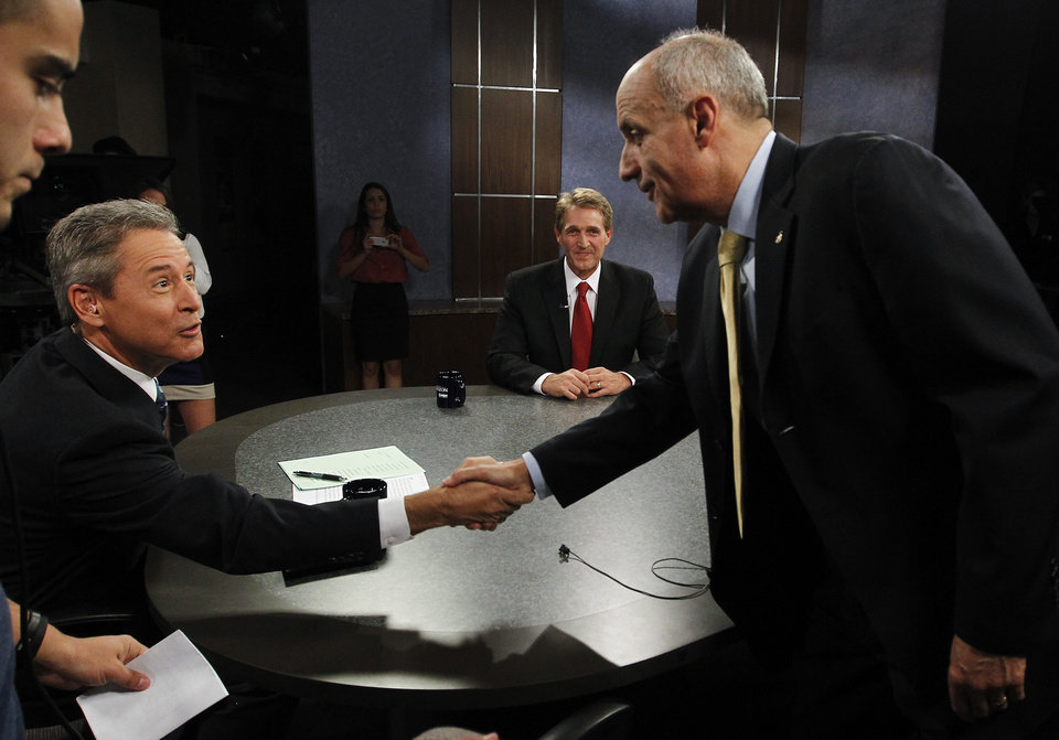 Photo -   Rep. Jeff Flake, R-Ariz., second from right, looks on as Democrat Richard Carmona, right, shakes hands with moderator Ted Simons, left, host and managing editor of Arizona Horizon at Eight, Arizona PBS, in the studio prior to an Arizona U.S. Senate debate Wednesday, Oct. 10, 2012, in Phoenix. The candidates are vying for the seat left open by retiring Sen. Jon Kyl, R-Ariz.(AP Photo/Ross D. Franklin)