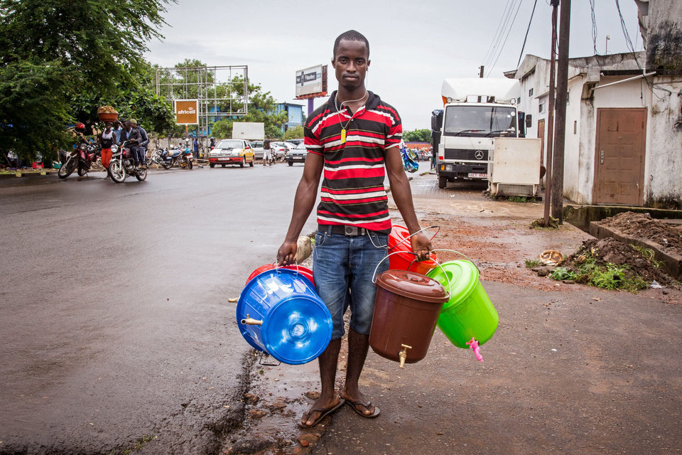 Photo - A street trader in Freetown sells plastic hand washing buckets, as demand for basic sanitation products has boomed during the Ebola crisis with a simple bucket and tap selling for around ten dollars in the city of Freetown, Sierra Leone, Wednesday, Aug. 6, 2014. The World Health Organization has begun an emergency meeting on the Ebola crisis, and said at least 932 deaths in four African countries are blamed on the virus, with many hundreds more being treated in quarantine conditions. (AP Photo/ Michael Duff)