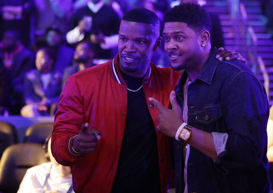Photo - Actor Jamie Foxx, left, poses for a photo with a fan during the second half of an NBA All-Star basketball game, Sunday, Feb. 17, 2019, in Charlotte, N.C. (AP Photo/Chuck Burton)