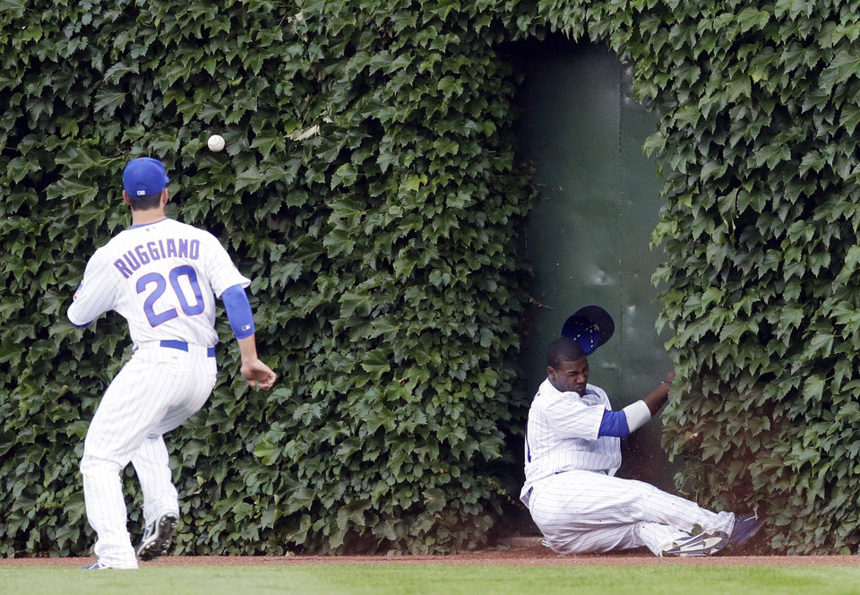 Photo - Chicago Cubs center fielder Junior Lake, right, can't make the catch on a double hit by Washington Nationals' Ryan Zimmerman as Chicago Cubs right fielder Justin Ruggiano chases the ball during the second inning of a baseball game in Chicago, Thursday, June 26, 2014. (AP Photo/Nam Y. Huh)