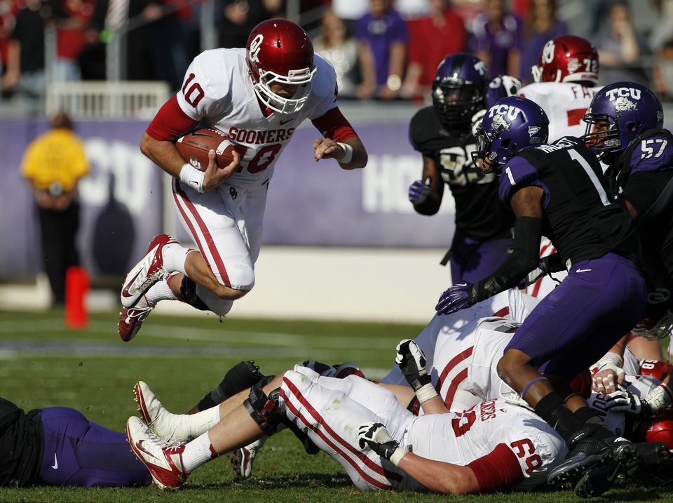 Oklahoma backup quarterback Blake Bell (10) leaps over Lane Johnson (69) for a first down as TCU\'s Chris Hackett (1) and Davion Pierson (57) attempt the stop in the second half of an NCAA college football game Saturday, Dec. 1, 2012, in Fort Worth, Texas. Oklahoma won 24-17. (AP Photo/Tony Gutierrez) ORG XMIT: TXTG113