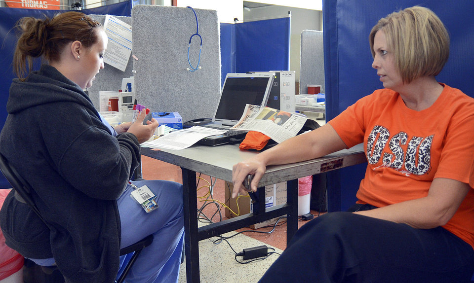 Photo - Rhonda Zander talks with a nurse before giving blood during this week's Oklahoma State University blood drive.  Photo by Adam Kemp, The Oklahoman