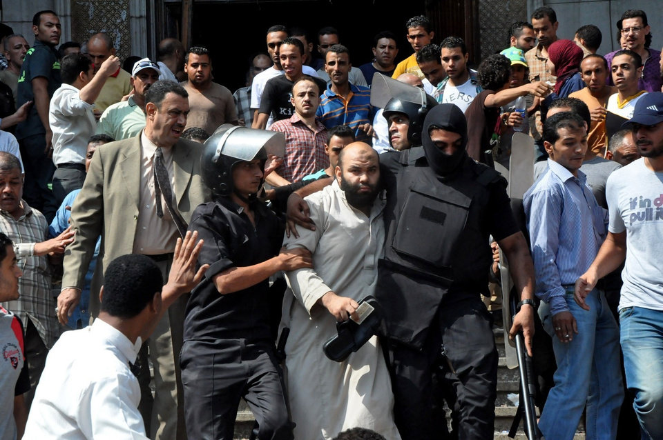 Photo - Egyptians security forces escort an Islamist supporter of the Muslim Brotherhood out of the al-Fatah mosque, after hundreds of Islamist protesters barricaded themselves inside the mosque overnight, following a day of fierce street battles that left scores of people dead, near Ramses Square in downtown Cairo, Egypt, Saturday, Aug. 17, 2013. Authorities say police in Cairo are negotiating with people barricaded in a mosque and promising them safe passage if they leave. Muslim Brotherhood supporters of Egypt's ousted Islamist president are vowing to defy a state of emergency with new protests today, adding to the tension. (AP Photo/Hussein Tallal)