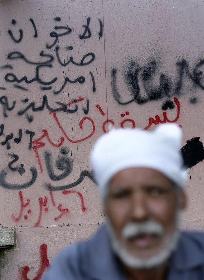 Photo - An Egyptian man walks past Arabic writing on a wall that reads,