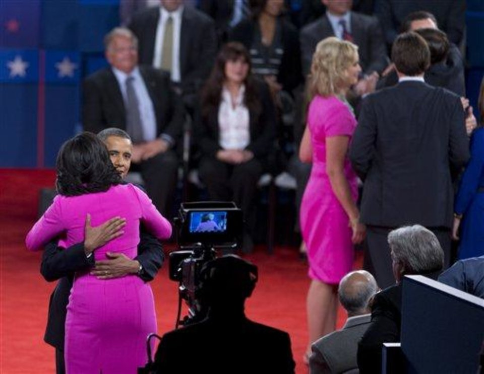 Photo - FILE - This Oct. 16, 2012 file photo shows President Barack Obama embracing first lady Michelle Obama on stage after presidential debate at Hofstra University in Hempstead, N.Y.  Every year fashion offers up the good, the bad and the ugly. But what the industry is really built on _ and consumers respond to _ is buzz.  The wives of the presidential candidates turned out to the second debate between Barack Obama and Mitt Romney in practically the same shade of hot pink. But they weren't by the same designer: Ann Romney's was by Oscar de la Renta, and Obama's by Michael Kors.  (AP Photo/Carolyn Kaster)