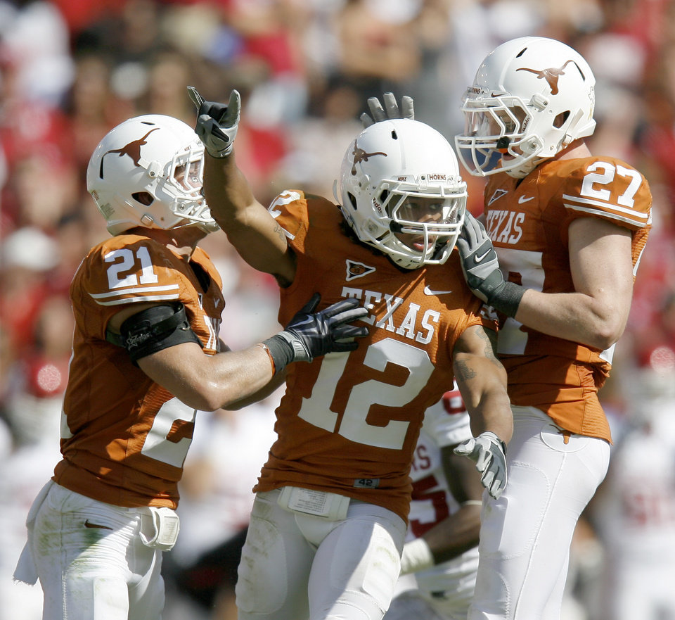 Photo - Earl Thomas, center, celebrates with Blake Gideon, left, and Nolan Brewster after an interception in the fourth quarter in the Red River Rivalry college football game between the University of Oklahoma Sooners (OU) and the University of Texas Longhorns (UT) at the Cotton Bowl in Dallas, Texas, Saturday, Oct. 17, 2009. Photo by Bryan Terry, The Oklahoman