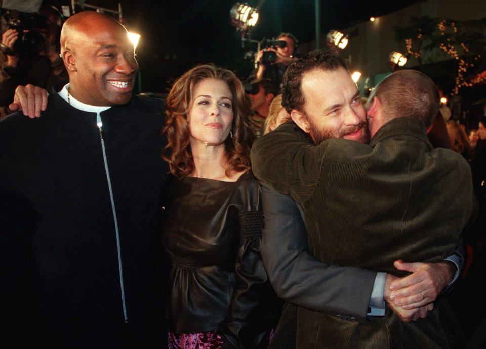 Photo -   FILE - In this Monday, Dec. 6, 1999 file photo, Michael Clarke Duncan, left, watches as Tom Hanks, second from right, hugs fellow cast member Doug Hutchison as his wife Rita Wilson looks on at the premiere of