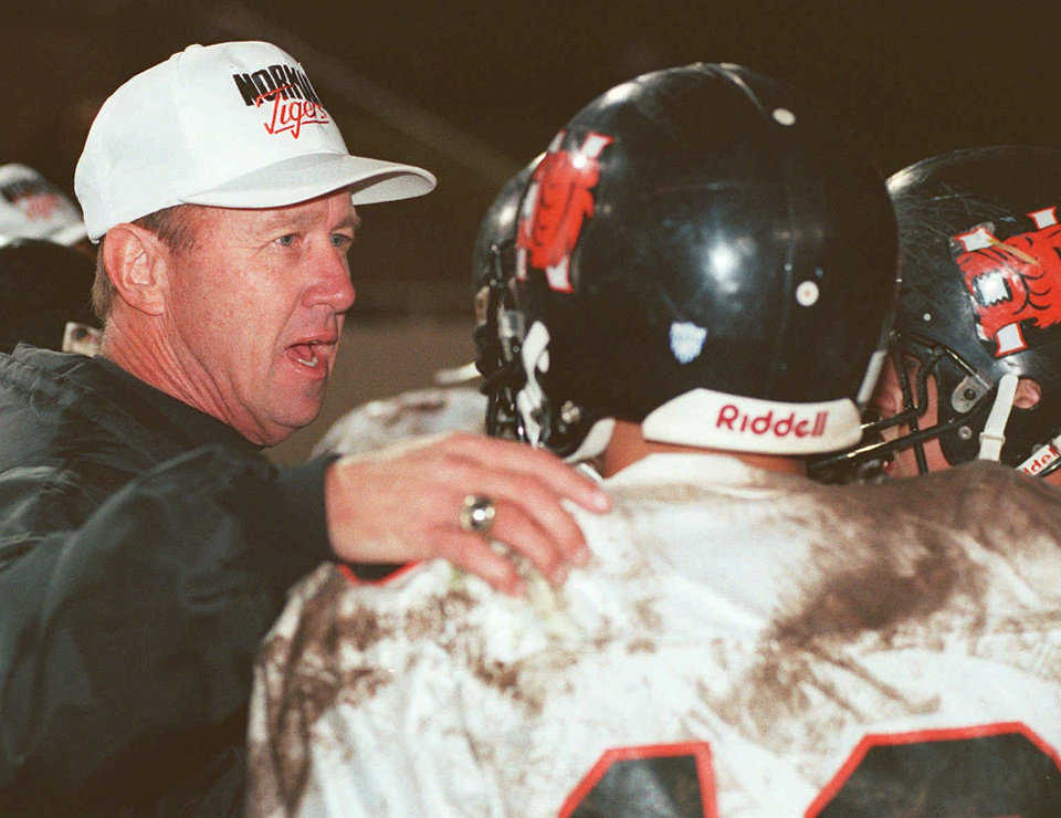 Photo - Norman high school football coach Cotton Wade talks to his players during a timeout. Back to camera is QB #16 Ryan Hurt. Photo from The Oklahoman Archive