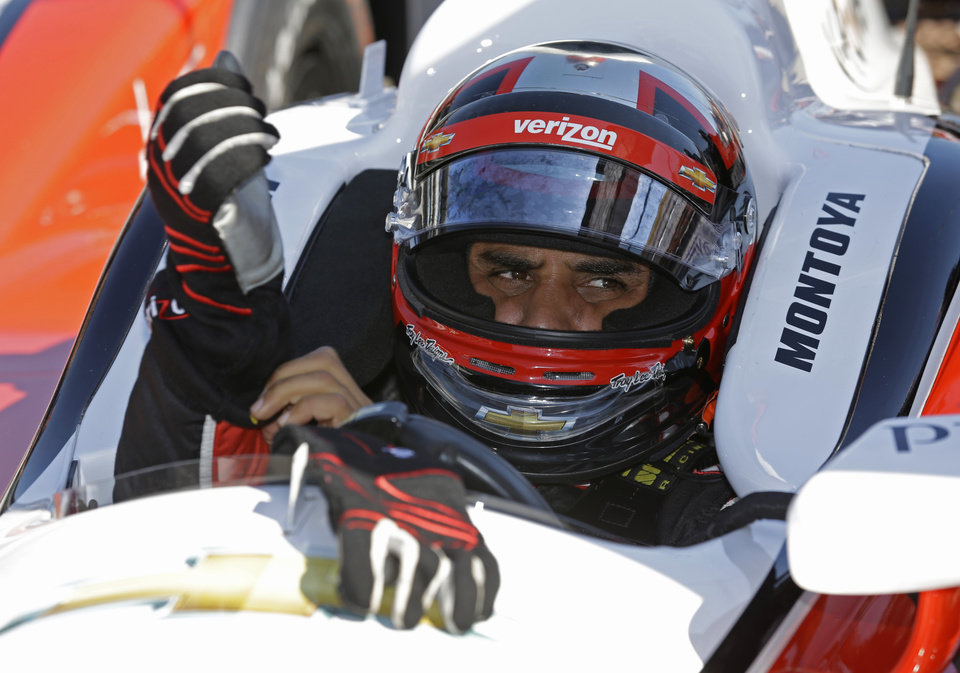 Photo - Juan Pablo Montoya, of Colombia, puts on his gloves as he prepares to drive on the final day of practice for the Indianapolis 500 IndyCar auto race at the Indianapolis Motor Speedway in Indianapolis, Friday, May 23, 2014. The 98th running of the Indianapolis 500 is Sunday. (AP Photo/Michael Conroy)