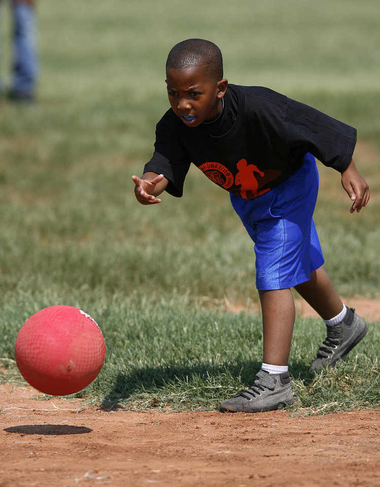 Terry Gaddis, 7, rolls a ball during a kickball tournament hosted by the Oklahoma City Police Department at South Rotary Park in Oklahoma City, Wednesday, June 27, 2012.  Photo by Garett Fisbeck, The Oklahoman
