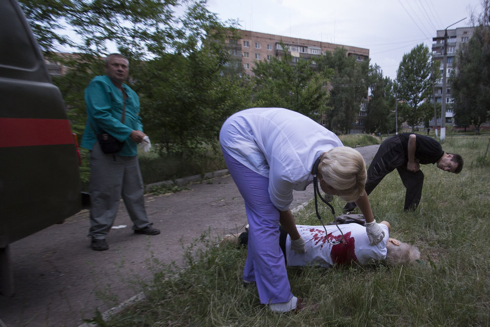Photo - Local ambulance medics run to the body of Olga Prokhorenko, 60, killed by shrapnel following a shelling from Ukrainian government forces in Slovyansk, Ukraine, Monday, May 26, 2014.  Exit polls from Sunday's first round of the new presidential election predict Petro Poroshenko will be elected president in this bitterly divided country, and he vowed