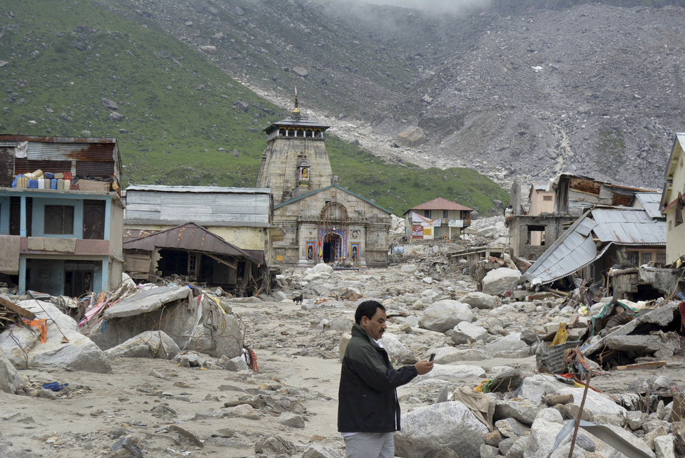 Photo - In this Thursday June 20, 2013, photo, a  pilgrim takes pictures of an area devastated following heavy monsoon rains at Kedarnath, in the northern Indian state of Uttrakhand. A joint army and air force operation are trying to evacuate thousands of people stranded in the upper reaches of the state of Uttrakhand where days of rain had earlier washed out houses, temples, hotels and vehicles leading to deaths of over a hundred people amid fears that the death toll may rise much higher. (AP Photo)