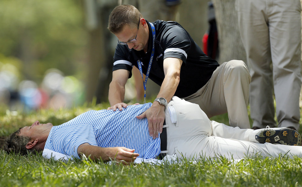 Photo - Wes Short Jr. receives attention to his back before teeing off on No. 5 during the third round of the U.S. Senior Open golf tournament at Oak Tree National in Edmond, Okla., Saturday, July 12, 2014. Photo by Nate Billings, The Oklahoman