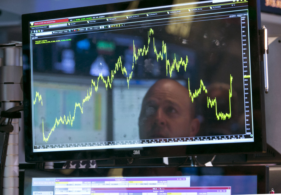 Photo - Specialist Jay Woods is reflected in one of the screens at his post on the floor of the New York Stock Exchange, Wednesday, June 18, 2014. U.S. stocks are little changed in early trading as investors wait for the latest policy action from the Federal Reserve. (AP Photo/Richard Drew)