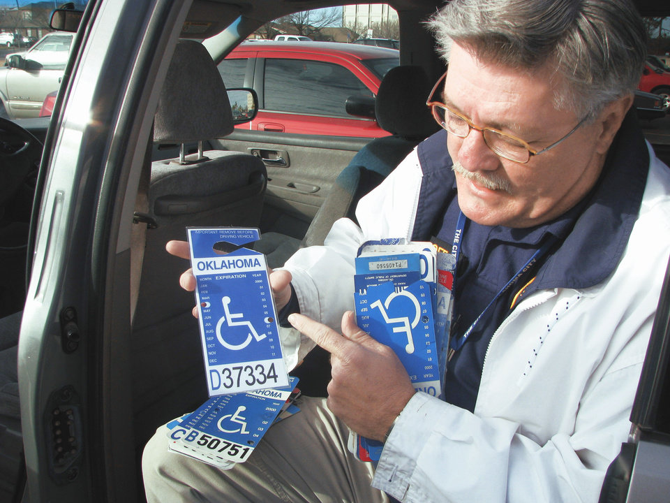 Photo - David Hoff, civilian officer for the Handicap Parking Enforcement Specialist program, holds bogus handicap parking placards he confiscated.  PHOTO BY VALLERY BROWN, THE OKLAHOMAN