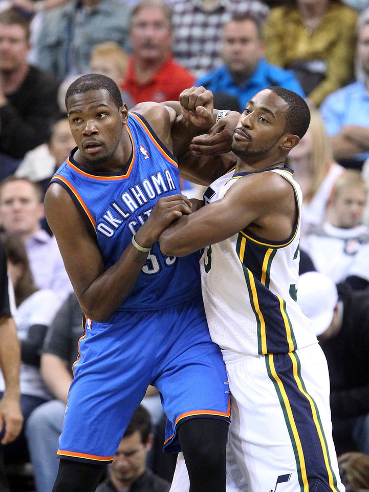 OKC's Thunder's Kevin Durant, left, battles for position with Utah's Mike Harris during the first half of the Thunder's season-opener in Salt Lake City. The game was still being played at press time. Go to NewsOK.com for game results. AP Photo