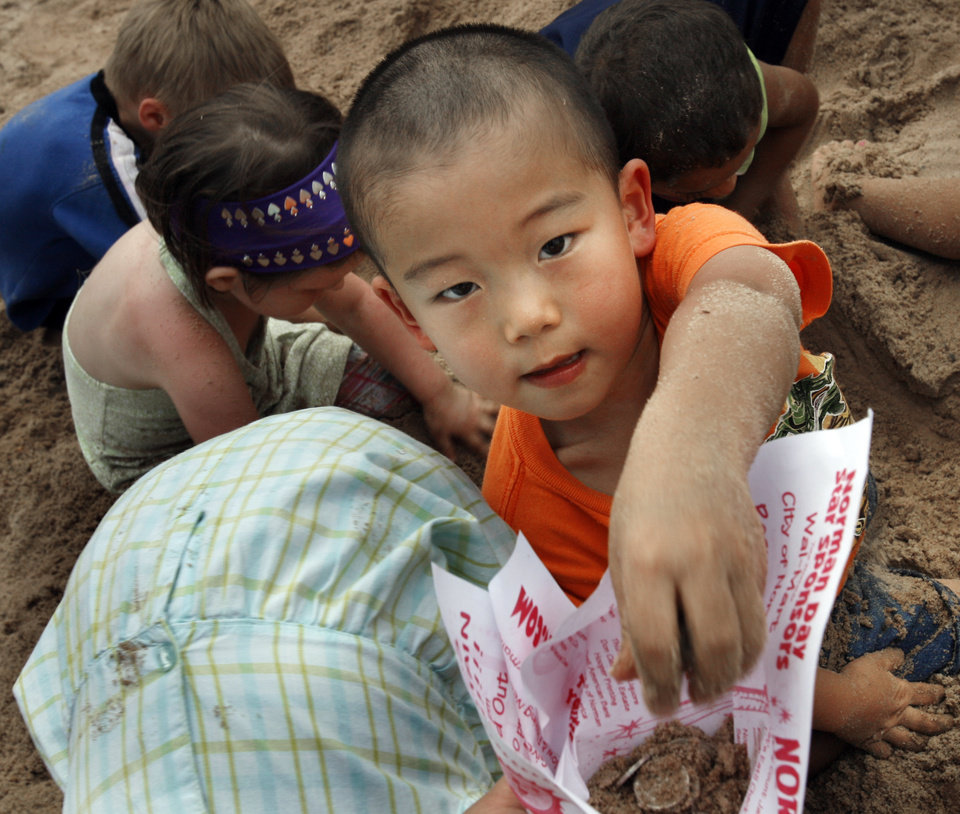 Jerry Xing, 4, from Norman, hands his parent coins found in the nickel search during Norman Independence Day Celebration at Reaves Park in Norman, Okla., on Saturday, July 4, 2009.     Photo by Steve Sisney, The Oklahoman