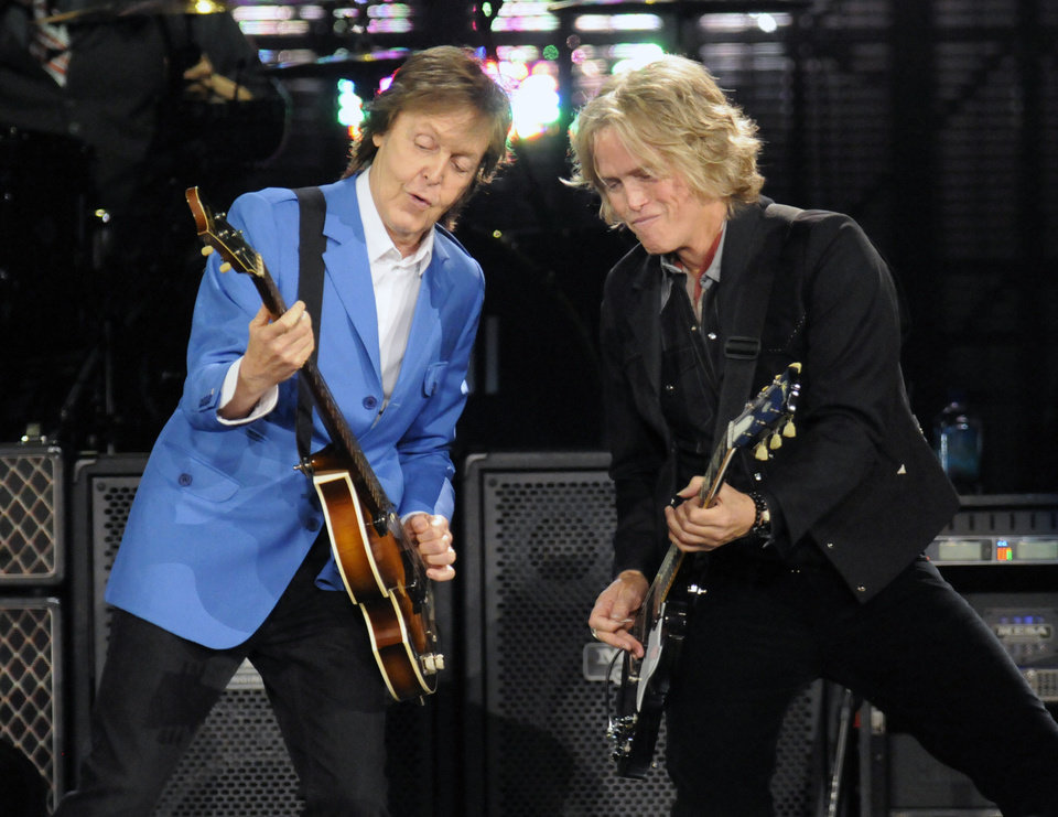 "Photo - Sir Paul McCartney, left, performs with band member Brian Ray during the ""Out There"