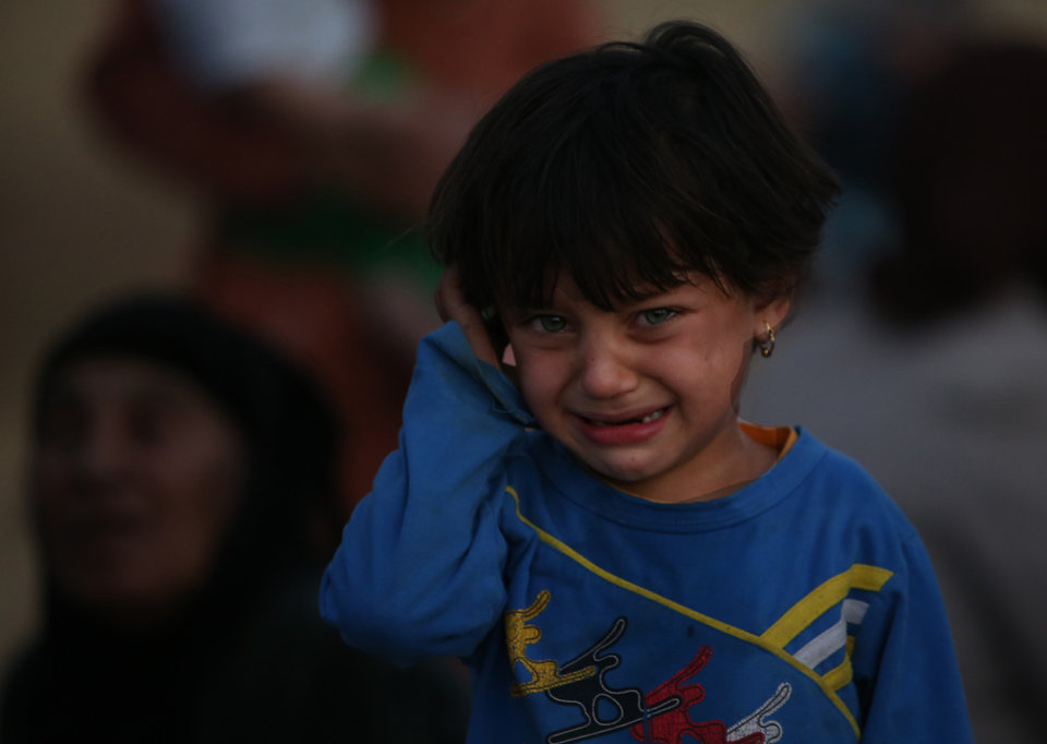 Photo - A fleeing Iraqi girl, cries as she settled with her family in a field near a Kurdish security forces checkpoint, in the Khazer area between the Iraqi city of Mosul and the Kurdish city of Irbil, northern Iraq, Wednesday June 25, 2014. Sunni insurgents who seized Iraq's second largest city attacked a nearby Christian village on Wednesday, bringing their fight closer to the largely Kurdish regions of northern Iraq which had remained so far largely untouched from the chaos sweeping the country. (AP Photo/Hussein Malla)