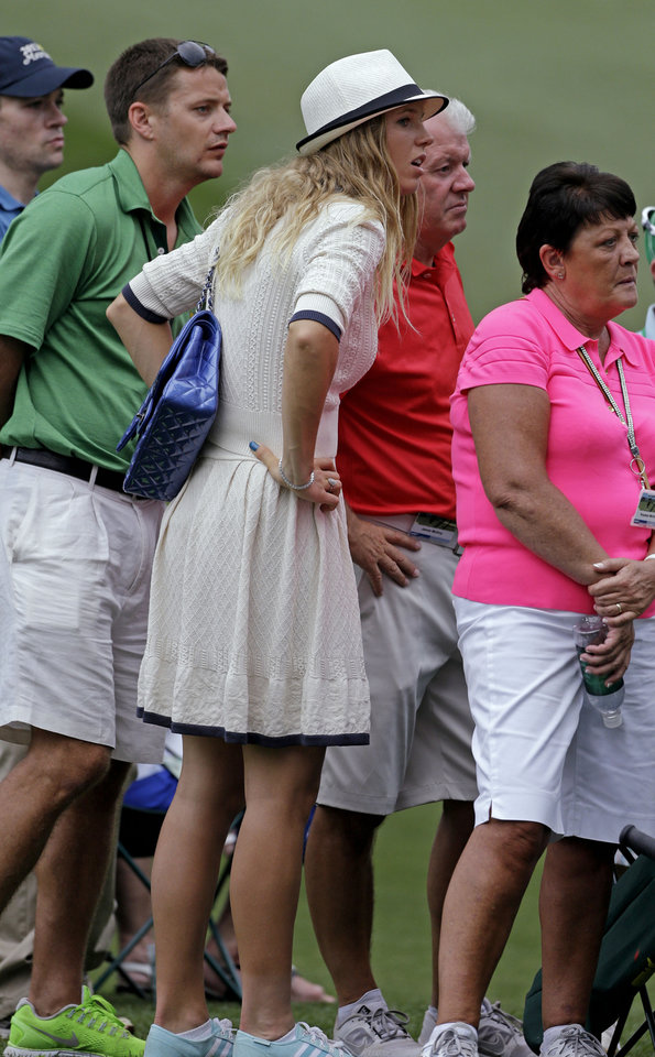 Photo - Tennis player Caroline Wozniacki watches Rory McIlroy, of Northern Ireland, with his father Gerry, right, during the first round of the Masters golf tournament Thursday, April 11, 2013, in Augusta, Ga. (AP Photo/David Goldman)