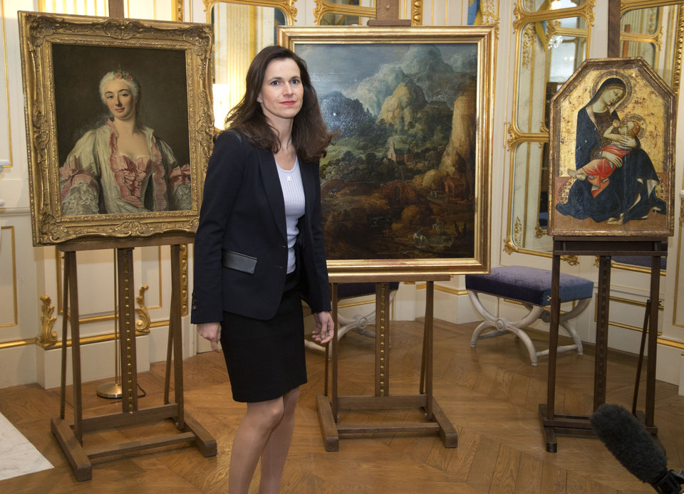 Photo - France's culture minister Aurelie Filipetti, arrives at a ceremony at the Culture Ministry in Paris, Tuesday, March 11, 2014, to return three paintings taken from their owners during World War II, background. The restitution is part of France's ongoing effort to return hundreds of looted artworks that Jewish owners lost during the war that still hang in the Louvre and other museums. (AP Photo/Michel Euler)