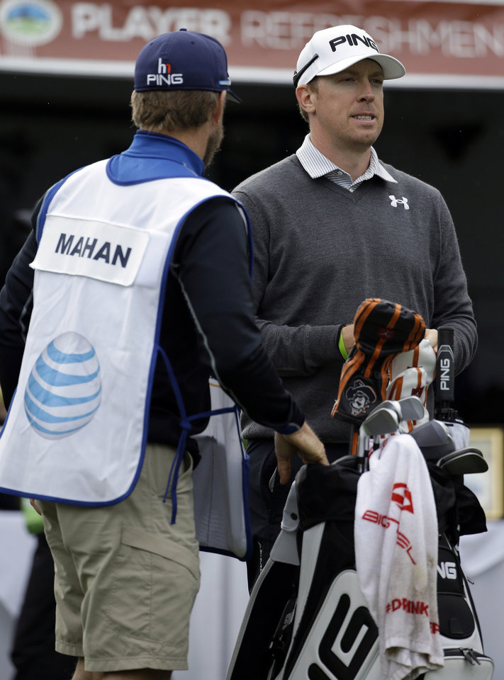 Photo - Hunter Mahan, right, waits to hit off the first tee on Friday, Feb. 7, 2014, during the second round of the AT&T Pebble Beach Pro-Am golf tournament on the Spyglass Hill Golf Course in Pebble Beach, Calif. (AP Photo/Ben Margot)