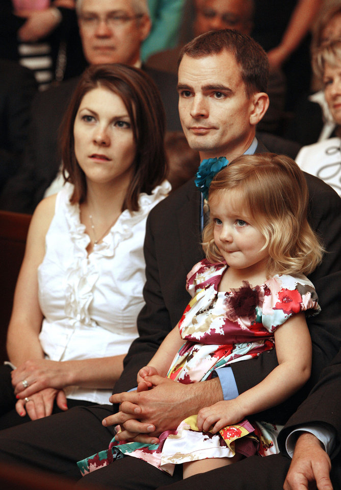 Photo - James Greiner sits with his wife Katie and daughter Lydia, age 2, in the council chamber before being sworn in as Ward 1 city councilman in Oklahoma City Tuesday, April 9, 2013.  Photo by Paul B. Southerland, The Oklahoman