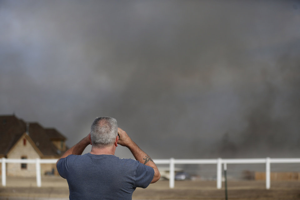 Photo - Kirk Ferguson watches a wildfire burn near his home near SE 164th Street as a wildfire burns in the area in southeast Oklahoma City, Okla., Sunday, Feb. 12, 2017. Photo by Sarah Phipps, The Oklahoman