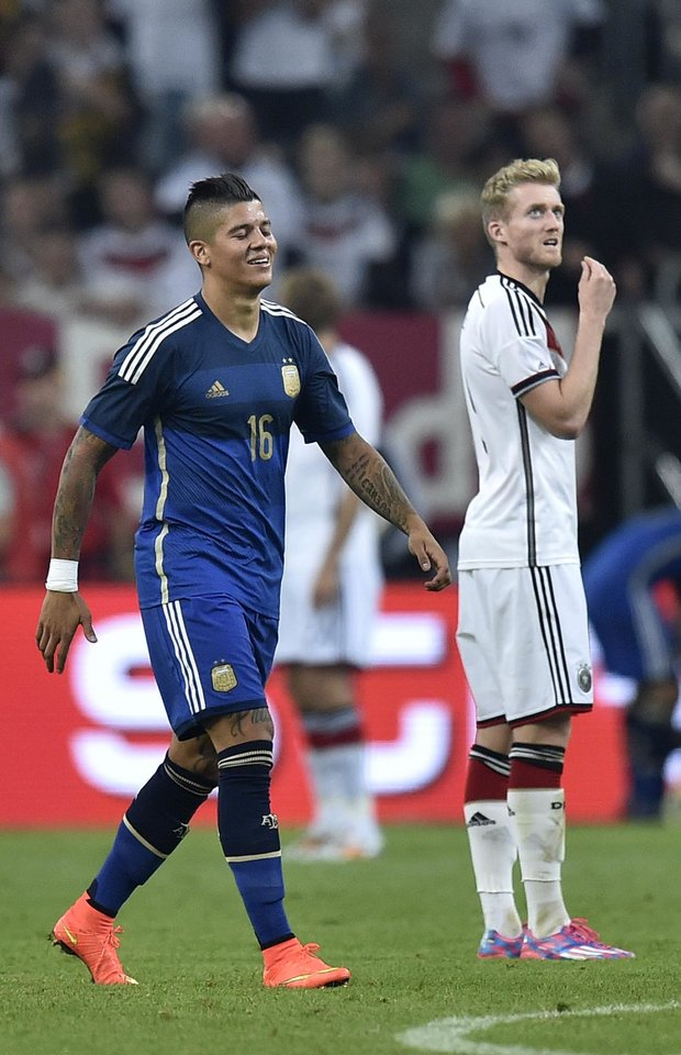 Photo - Argentina's Marcos Rojo smiles as he walks past Germany's Andre Schuerrle during the friendly soccer match between Germany and Argentina in Duesseldorf, Germany, Wednesday, Sept. 3, 2014. (AP Photo/Martin Meissner)