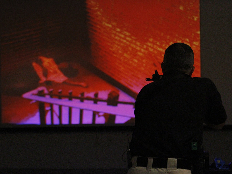 Edmond police Sgt. Jeff Richardson demonstrates a new simulator that allows officers to shoot different crime scenes in Edmond, Thursday 26, 2012. Photo By Steve Gooch, The Oklahoman
