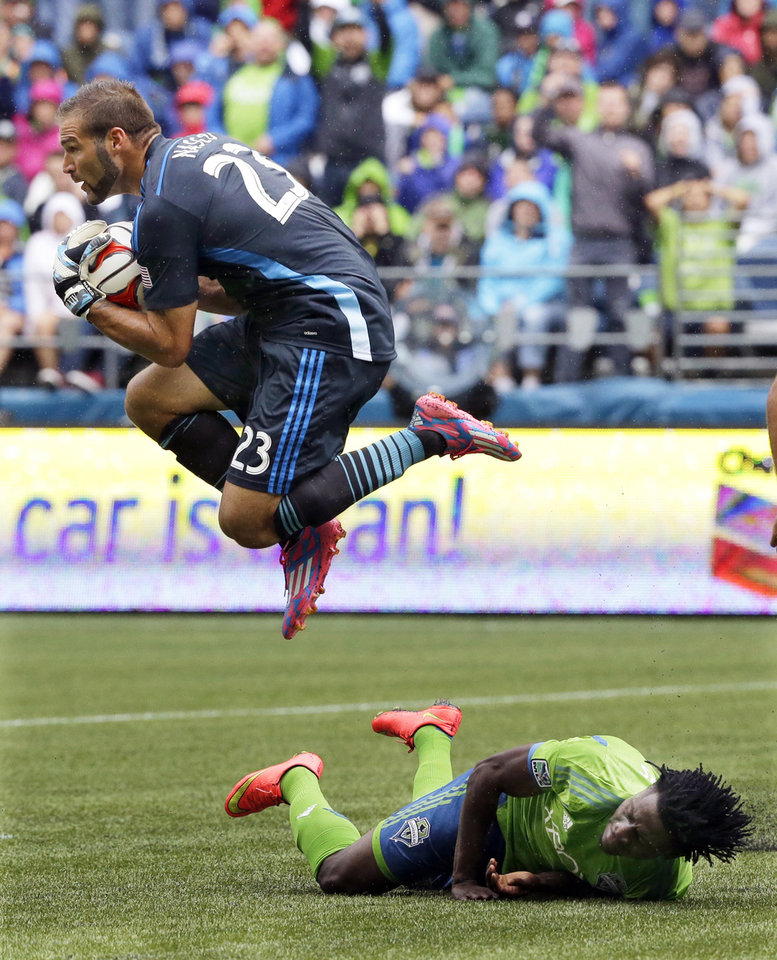 Photo - Colorado Rapids goalkeeper Joe Nasco leaps over Seattle Sounders' Obafemi Martins in the second half of an MLS soccer match, Saturday, Aug. 30, 2014, in Seattle. The Sounders defeated the Rapids 1-0. (AP Photo/Ted S. Warren)